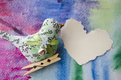 Textile toy bird on watercolor paper background with space for text.Paper Heart - a place for inscription requests Royalty Free Stock Images