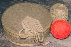 Textilen täckte asken med rött garn och tvinnar arkivfoton