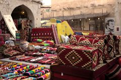 Textiles in doha souq. SOUQ WAQIF, DOHA, QATAR - OCTOBER 23, 2017: Textiles on sale in Souq Waqif in Qatar, Arabia, with a poster of the Emir showing loyalty Royalty Free Stock Photo
