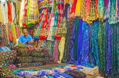 Textiles in Vakil Bazaar, Shiraz, Iran. SHIRAZ, IRAN - OCTOBER 14, 2017: The merchant in textile stall of Vakil Bazaar among colorful fabrics, decorated with royalty free stock photography