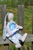 Textilhandgemachtes Spielzeug auf einem alten Bretterzaun stockfotos