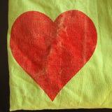 Textilhintergrund mit rotem Herzen Stockbilder