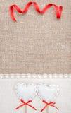 Textilhjärtor, band och linnetorkduk på säckväven Royaltyfri Bild