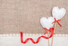 Textilhjärtor, band och linnetorkduk på säckväven Royaltyfri Foto