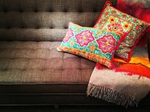 Textilsoffa som dekoreras med ljusa utsmyckade kuddar Arkivbilder