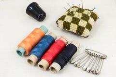 Textiltyg för att sy, tillbehör för handarbete på ny textilbakgrund Rulle av tråden, sax, fingerborg, tapemeasure, arkivfoton