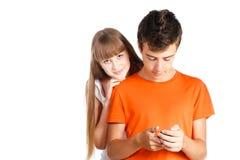 texting与他的女朋友的少年男孩 库存照片