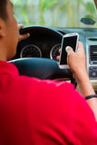 texting亚裔的人,当驱动时 免版税图库摄影