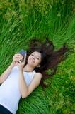 texting亚洲逗人喜爱的女孩的草甸 免版税图库摄影