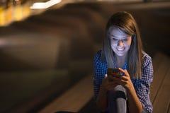 texting的妇女 看流动手机读书的特写镜头年轻愉快的微笑的快乐的美丽的妇女女孩送sms 免版税库存图片