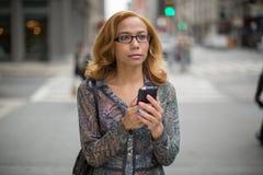 Texting κινητό τηλέφωνο γυναικών του Λατίνα στην πόλη Στοκ Φωτογραφία