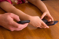 Texting. Father teaching young daughter to phone text. Only the hands are in the picture Stock Photo