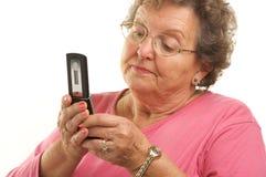 移动电话高级texting的妇女 免版税库存图片