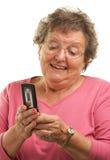 移动电话高级texting的妇女 免版税图库摄影