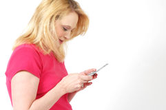 Texting. Blond woman text messaging on her cell phone. White background, Copy space to the right of her Royalty Free Stock Photo