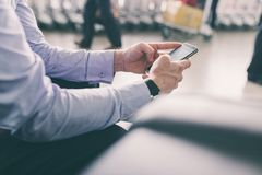 Texting at the airport. Cropped image of businessman texting while waiting at the airport Royalty Free Stock Photos