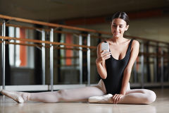Texting during Ballet Class. Beautiful smiling ballerina sitting on floor in dance studio elegantly and holding smartphone in hand texting or taking photo royalty free stock photo