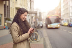 Texting brunette woman reads her phone and smiles. Texting brunette woman reads a message on her mobile phone and smiles while being unaware of approaching bus Royalty Free Stock Photography