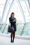 Texting business lady. Full-length portrait of Japanese female manager standing outdoors and texting Stock Photo