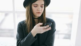 Texting cellphone chatting young girl in stylish hat. Casual lifestyle video footage. Online communication stock footage