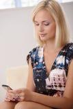 Texting consideravelmente louro no telefone móvel Imagem de Stock Royalty Free