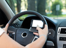 Texting and Driving. Closeup of a smart phone with a female hand texting and driving