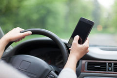 Texting and driving. Person texting while driving the car Stock Images
