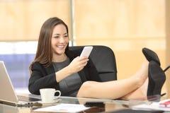 Texting executivo relaxado no telefone esperto Imagem de Stock Royalty Free