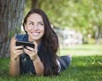 Texting femenino joven en el teléfono celular afuera Foto de archivo libre de regalías