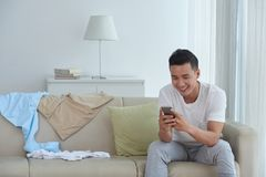 Texting with friends. Handsome Asian young man texting with friends when resting at home Royalty Free Stock Images