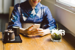 Texting girl. Cropped image of smiling Japanese girl in kimono sitting at the table and texting Royalty Free Stock Photography