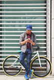 Texting guy. Young man with bicycle standing outdoors and texting Royalty Free Stock Photos