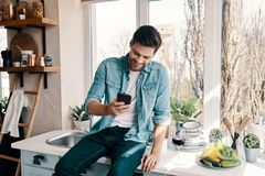 Texting his girlfriend. Handsome young man in casual wear smiling and using his smart phone while sitting in the kitchen at home stock photos