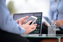 Texting kolega Ufny młody człowiek trzyma mądrze telefon i patrzeje je w kostiumu podczas gdy siedzący przy jego działaniem Zdjęcia Royalty Free