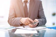 Texting kolega Ufny młody człowiek trzyma mądrze telefon i patrzeje je w kostiumu podczas gdy siedzący przy jego działaniem Fotografia Royalty Free
