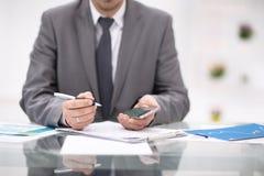 Texting kolega Ufny młody człowiek trzyma mądrze telefon i patrzeje je w kostiumu podczas gdy siedzący przy jego działaniem Zdjęcia Stock