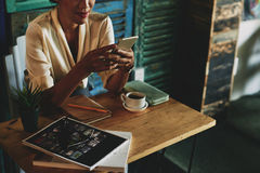 Texting lady. Cropped image of woman having cup of coffee in cafe and texting Stock Photography