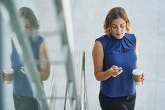 Texting lady. Pretty woman standing on stairs and texting royalty free stock photos