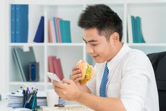 Texting at lunch. Young office worker eating burger and texting during the break Stock Photo