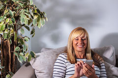 Texting maduro de sorriso da mulher fotos de stock