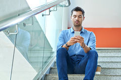 Texting man. Texting young man sitting on stairs and texting Royalty Free Stock Photo