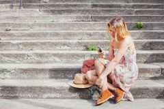 Texting on mobile, woman using smartphone app. While sitting on the stairs, social network stock images