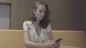 Texting no smartphone Mulher que usa o telefone móvel filme