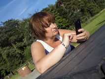 Texting in the park Royalty Free Stock Images