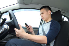 Texting on phone while driving. A male driver texting on a cellphone while driving Stock Photo