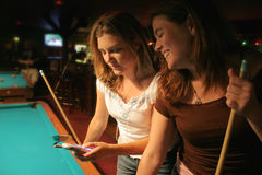 Texting at the pool hall. Two beautiful women texting or looking at a picture on a cellular phone stock photography
