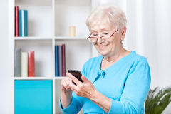 Texting senior. Smiley senior woman texting on mobile phone Stock Photography