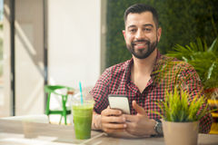 Texting in a smoothie shop Royalty Free Stock Images