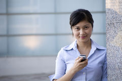 Texting some colleagues. Young lady texting on mobile phone smiling Royalty Free Stock Images