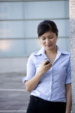 Texting some friends. Young professional woman writing text message on mobile phone Stock Image